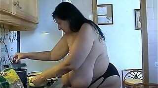 Granny with Giant saggy udders cooks in topless. Massive hanging Cow Udders